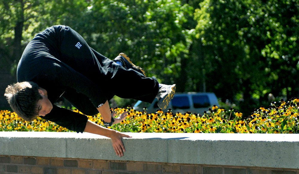 Twin Cities Parkour member Damon Curry does a body spin Wednesday near Jones Hall. Parkour, the art of moving over obstacles from point to point, is gaining popularity in the United States.