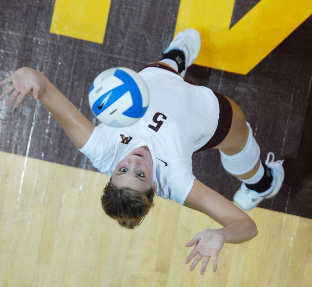 Sophomore middle blocker Lauren Gibbemeyer serves in a game at the Sports Pavilion last year.