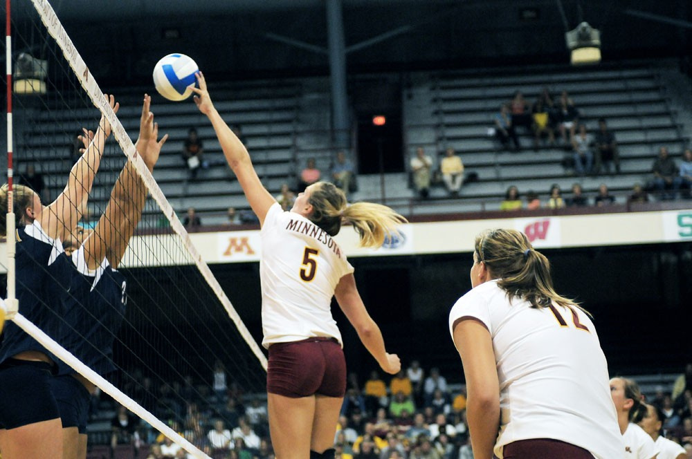 Sophomore middle blocker Lauren Gibbemeyer ties to finish off a kill at the Sports Pavilion. Gibbemeyer and the Gophers will host three games this weekend against some less flashy competition that weeks past.