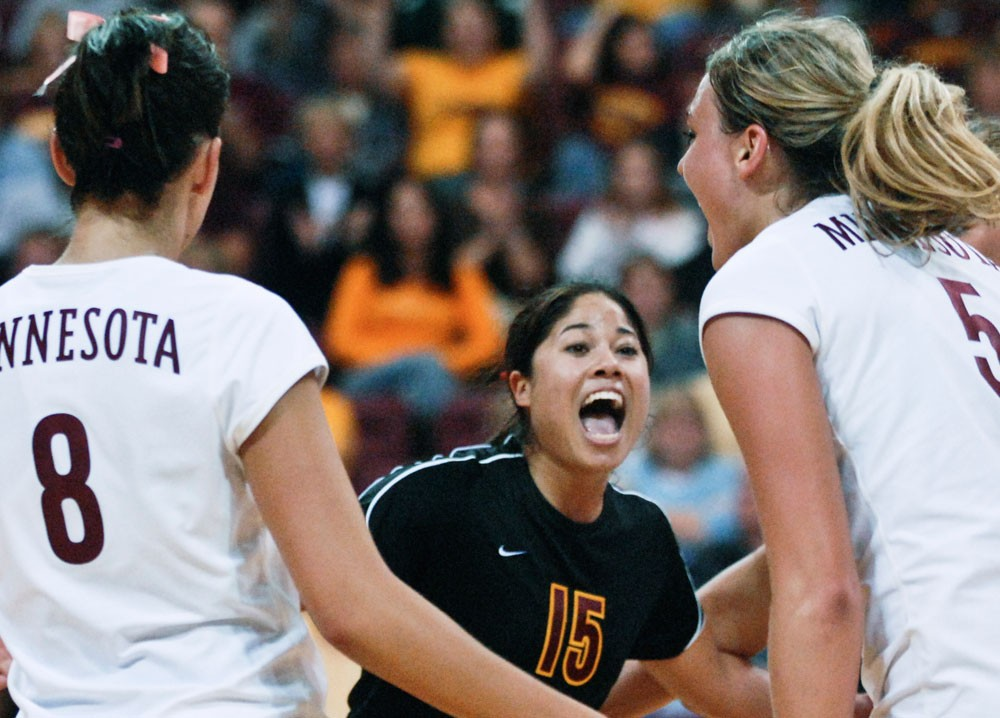 Junior libero Christine Tan (center) celebrates with teammates Rachel Hartman (left) and Lauren Gibbemeyer (right) in a match at the Sports Pavilion.