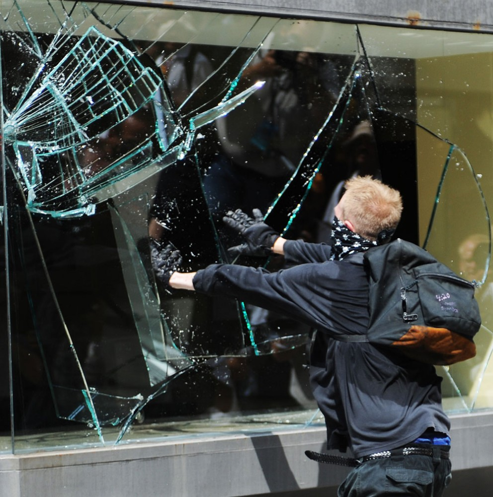 An anarchist protester smashes in the window of a department store in downtown St. Paul on Monday afternoon. The anarchist's left a trail of destruction in their wake including a smashed police car.