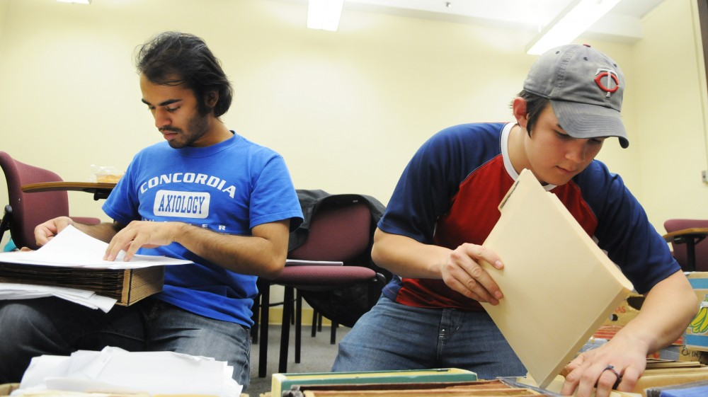 Debate team members Arif Hasan, left, and Logan Chin organize information Wednesday night in Folwell Hall. The team, in its second year, is one of the top 20 college debate teams in the country.