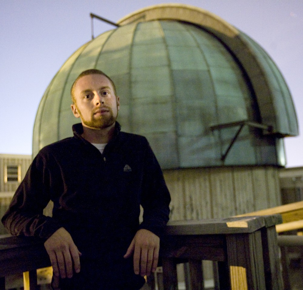 Graduate astronomy student Dan Weisz stands in front of the telescope observatory on the roof of the Tate Lab of Physics on Monday.  Weisz is part of a group of researchers using the Hubble telescope to compare the development of different galaxies.