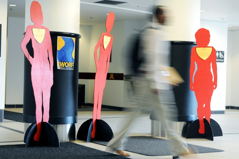 A walker strides past a display put up as part of October's Domestic Violence Awareness Month in Yudof Hall on Wednesday. Each cutout represents a different victim murdered in Minnesota in 2007 as a result of domestic violence.