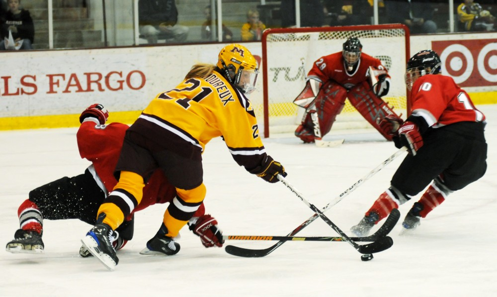 Freshman Monique Lamoureux closes in on the Ohio State goaltender in last weekends series against the Buckeyes. Lamoureux along with her sister Jocelyne and freshman Sarah Erickson have a strong bond that has helped the trio to a successful start to the season.