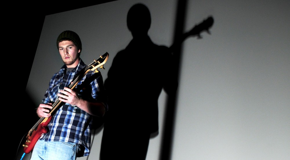 Centennial Hall representative Jake Gau plays bass guitar in the talent round of the Mr. Superblock fashion show in Coffman Theater on Tuesday.