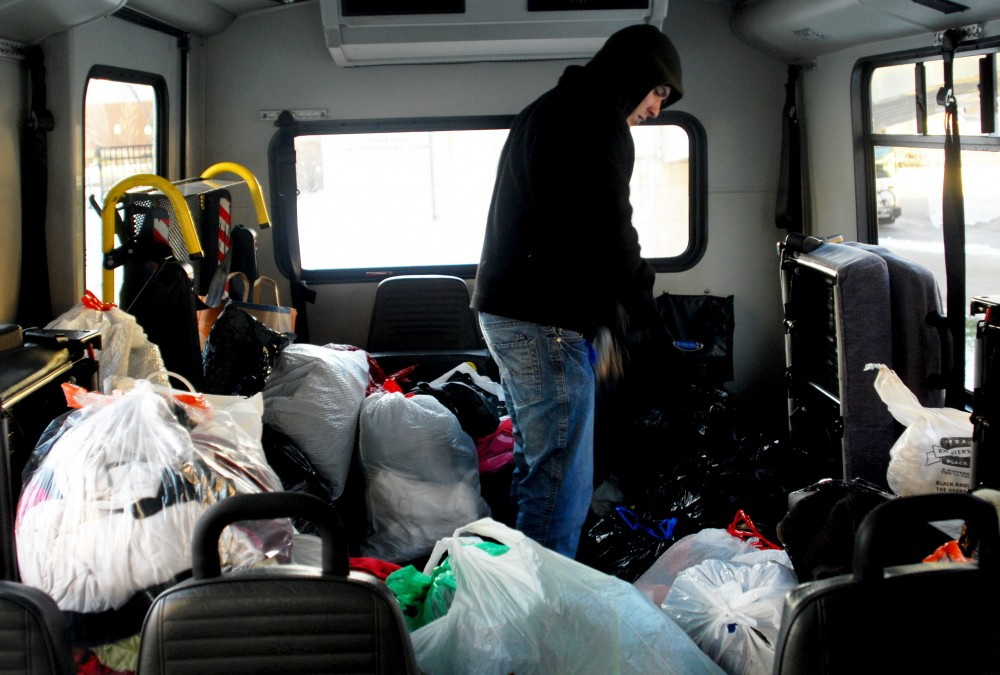 "Sociology senior Matt Walz counts bags of clothing donated during the ""Fill the Bus"" clothing drive on Monday outside Coffman Union. The more than 3,000 clothing items donated will be given to People Serving People homeless shelter in Downtown Minneapolis."