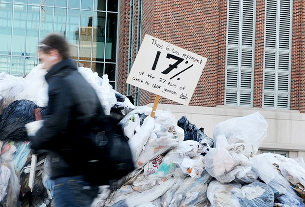 A passerby walks past more than six tons of garbage in front of Coffman Union on Wednesday. The temporary landfill was part of RecycleMania, a national recycling competition in which over 500 schools compete.