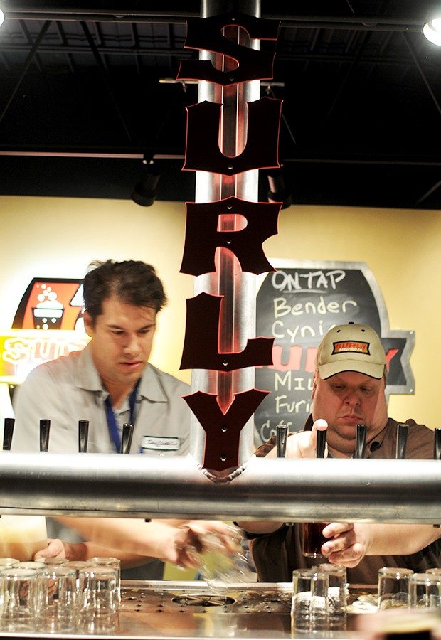 Surly owner Omar Ansari, left, and employee Keith Doten, right, serve a variety of brews for tour participants to taste test Friday.  The brewry, located in Brooklyn Center, offers tours by reservation Friday evenings.