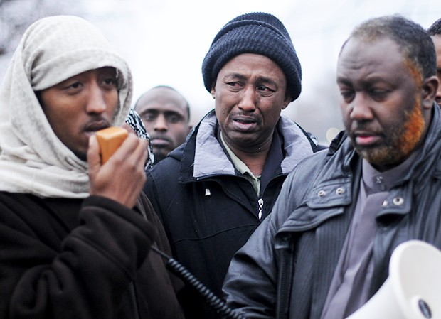 Ahmed Gulad's father, center, holds back tears as his son Assad Ali, left, speaks about his slain older brother Wednesday afternoon in north Minneapolis.