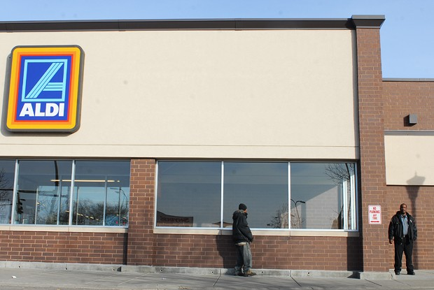 A security guard keeps watch outside an Aldi on Franklin Avenue, where people often sell their food stamps in exchange for cash.