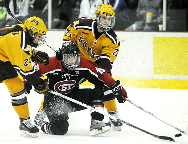 Freshman forward Monique Lamoureux (right) and freshman defenseman Anne Schleper battle for the puck during Saturday's WCHA title clinching win over St. Cloud State.