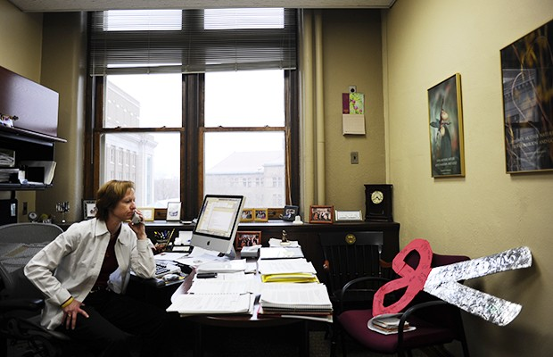 Associate to the President Lynn Holleran sits in her office with the symbolic pair of scissors that was delivered to her by a group of protesters Friday who wanted to cut the University's contact with Russell Athletics.