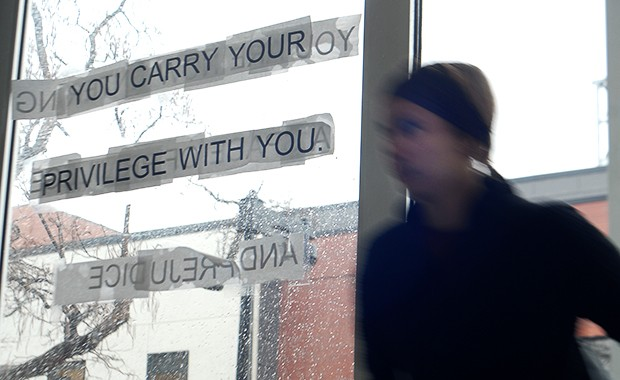 "A student walks past a statement of protest Monday in the Barbara Barker Center for Dance. The statement is part of ""THIS,"" a more than month long protest by anonymous students who feel institutional racism is an existing problem in the dance program."