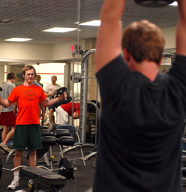 Gym goers lift weights Monday at the University Recreation Center.