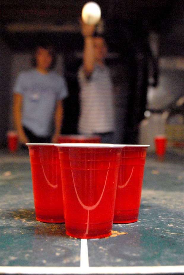 University of Minnesota seniors Christopher Meskimen and Phillip Petersen team together for a game of beer pong in their basement Sunday.  Neither said they would be affected by the discontinuation of the game in bars since they prefer to play at home.