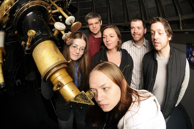 Astrophysics senior Tessa Vernstrom peers into the hundred year old telescope in Tate hall as other astrophysics graduate and undergraduate students look on. In honor of the international year of astronomy there will be public viewings at the telescope every Friday night.