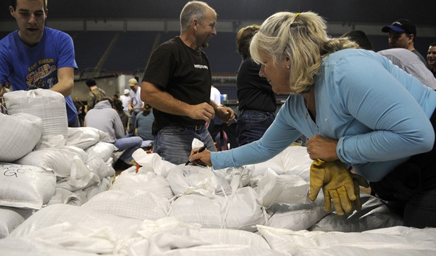 North Fargo resident and schoolteacher Cathy Speral writes messages on sandbags late Thursday evening at the Fargodome. Speral said she hoped it would boost the spirits of volunteers working on the front lines.