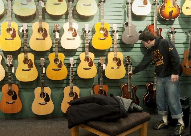 A customer shops for instruments in the basement level of The Podium, a family-owned Dinkytown guitar shop open since 1959.