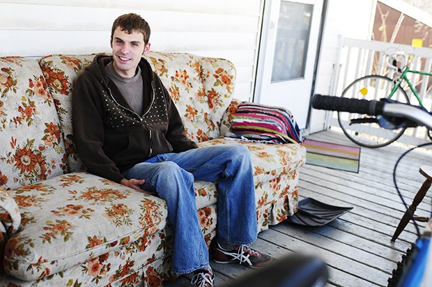 University microbiology senior Jon Strong sits on his porch Friday after the couch ban was officially overruled at a Minneapolis City Council meeting.