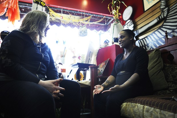 Store co-owner Sarah Dorman  left, applies henna Monday to customer and Plymouth resident Christina Gholson, right, at her store.