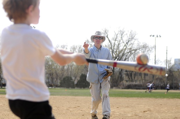Southeast Como resident Frederick Bethke tosses a pitch to his son Stefan, 8, at Van Cleave Park on Saturday. Minneapolis parks are currently controlled by an independent, elected park board, but there has been a recent move by some local Council Members to disband the board and cede control of the parks to the city.