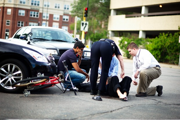 University of Minnesota economics instructor Lei Guo lays on the ground after being hit by a car at approximately 8:40 a.m. Thursday morning while riding his bicycle at the intersection of 19th Avenue SE and 2nd Street S.
