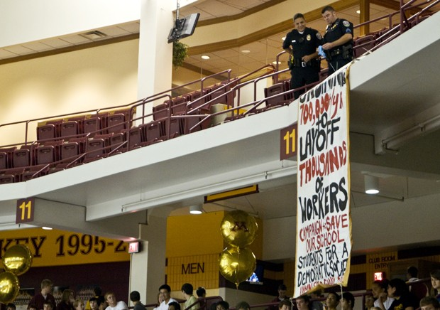UMPD officers take down a banner that demonstrators released during Convocation at Mariucci Arena on Thursday.