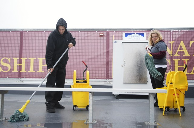 University of Minnesota students and general student workers for TCF Bank Stadium Jeremiah Schadegg, left, and Katie Gullifer mop up a spill before the football game Saturday.