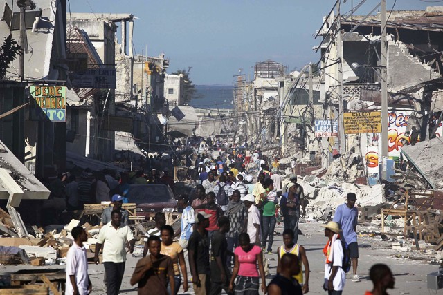Earthquake survivors walk amidst collapsed buildings and rubble in downtown Port-Au-Prince, Thursday, Jan. 14.