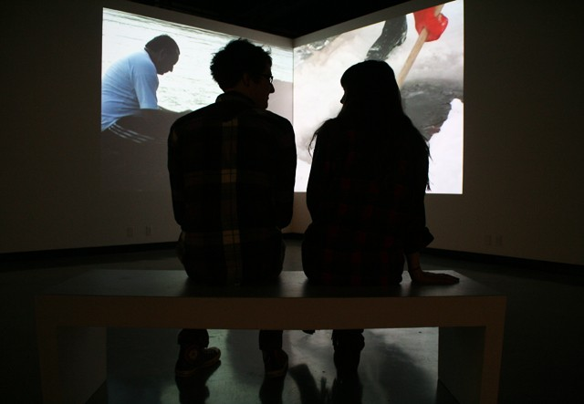 Sophomores Brenden Gerber and Elsabet Roth watch a video at the faculty exhibition in the Katherine E. Nash Gallery on Tuesday.  Faculty work will be shown at the Regis Center for art through February 18th.