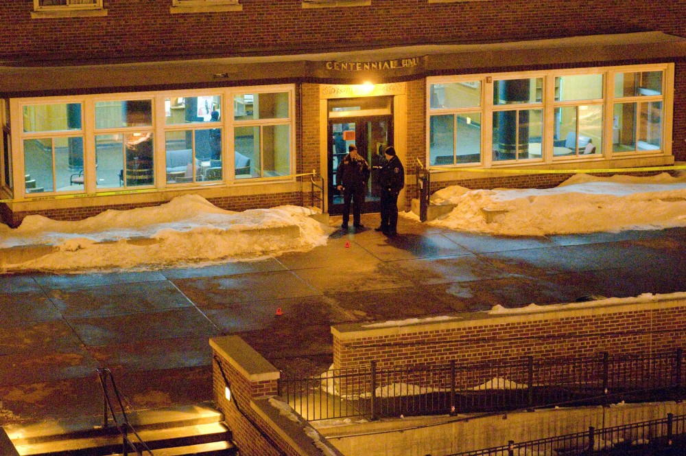 Police officers stand in front of Centennial Hall Tuesday morning where the shooting occurred.