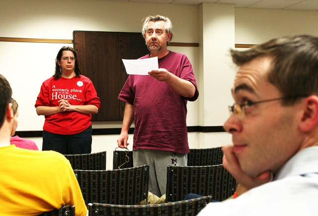 Paul Scheurer passes a resolution at the DFL caucus in Coffman Memorial Union on Tuesday that would give University of Minnesota Police more incentive to live on campus in order to increase their presence in the community.