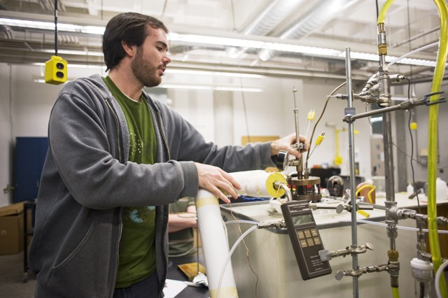 University graduate student Brandon Hathaway explains the process of biomass gasification Monday in the Mechanical Engineering building.