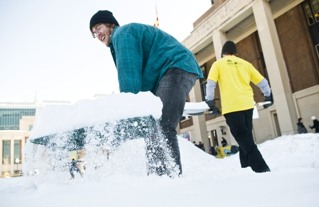 University sophomore Christopher Swanson shovels snow with other Beyond Coal members Thursday in front of Coffman Union to form a