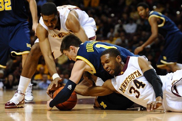 Gophers senior forward Damian Johnson (34) and sophomore center Ralph Sampson III fight for the loose ball against Michigan guard Stu Douglass (1) during the first half of Minnesota's 71-63 loss at Williams Arena on Thursday night.