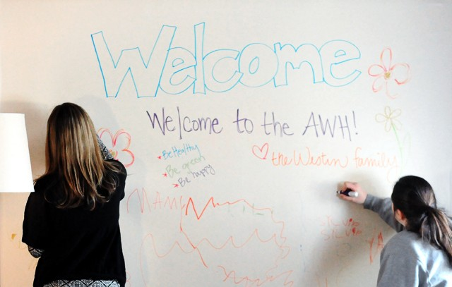 Willings, left, and Fox write welcome messages Sunday on the common room white board to the eight new residents.