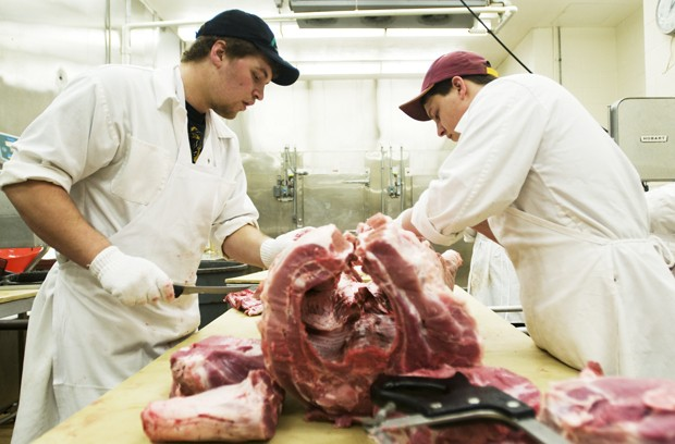 Animal science juniors Chris Dahlke, left, and Jason Ertl, right, cut up a pig Wednesday to be sold at a meat sale in the Andrew Boss Lab.