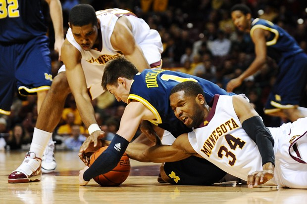 Gophers senior forward Damian Johnson (34) and sophomore center Ralph Sampson III fight for the loose ball against Michigan guard Stu Douglass (1) during the first half of Minnesota's 71-63 loss at Williams Arena.