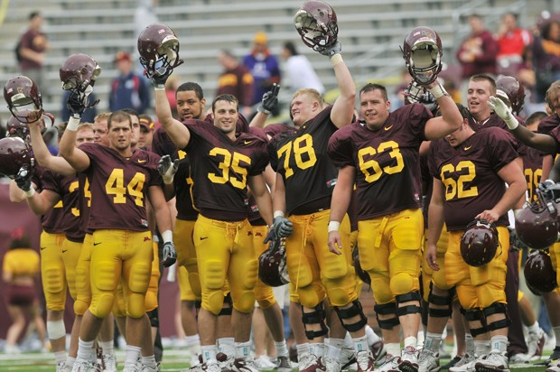 Players salute the crowd after a preseason scrimmage game at the TCF Stadium, Saturday.