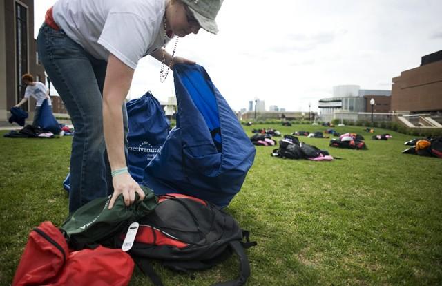 Psychology senior Kristine Volovsek picks up backpacks Monday from the Coffman Union lawn.