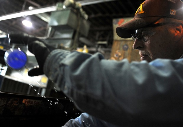 Warehouse foreman Dennis Treger sorts bottles at the Como Recycling Facility.