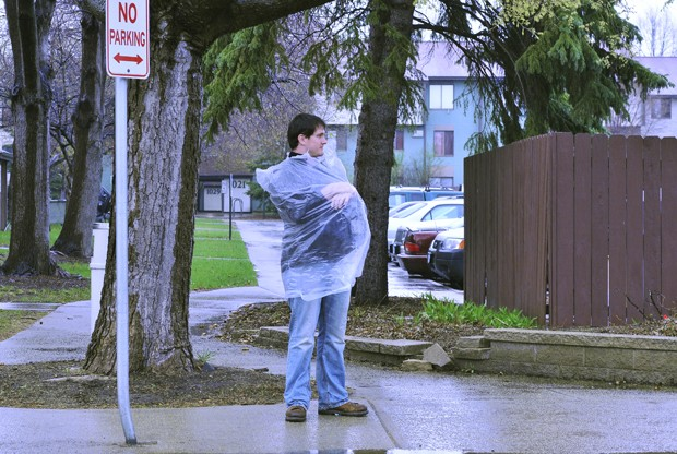 Senior Joe Barten uses a garbage bag as an improvised raincoat while waiting for a bus in St. Paul.