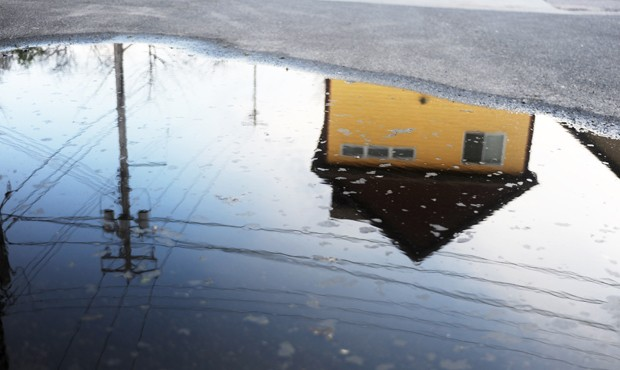 A Dinkytown house is reflected in a puddle.