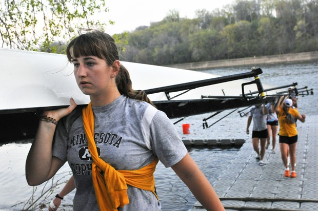 Sophomore and varsity rower Debbie Brzozowski helps her teammates return a boat after an early morning practice.