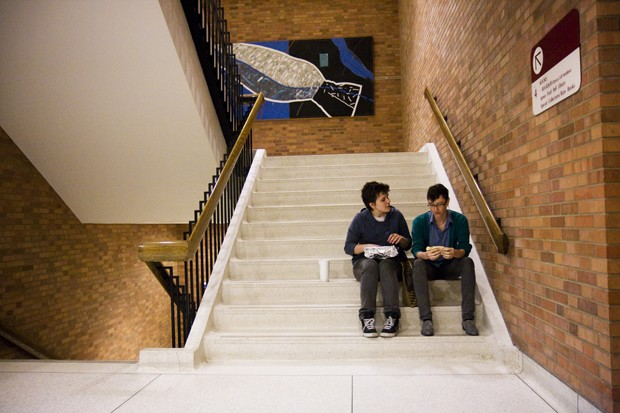 University junior Sophie Shank, left, and senior Sheena Meddaugh eat soft tacos from Chipotle in the stairwell of Wilson Library.