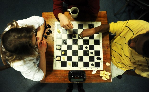 Sophia Anastazievsky, left, Melvin Lee and Yakob Wakjera discuss a recent game of chess at Hard Times Cafe.