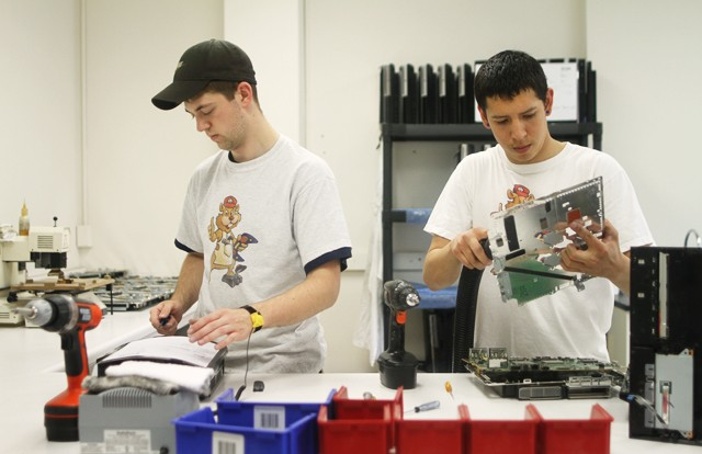 University senior Nick Wiebusch  and junior Ben Kenote  each clean and repair a PlayStation  3 on Friday.  Both are employees at Gophermods, a game console and iPhone repair business started by a University student.