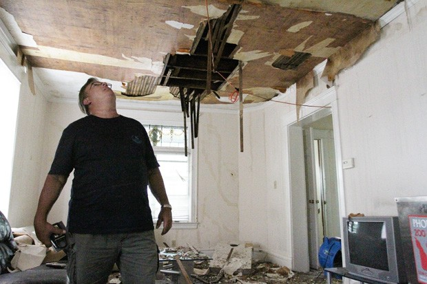 Landlord Tim Buffham examines the damage in his southeast Como rental property caused by a fire on Saturday afternoon.