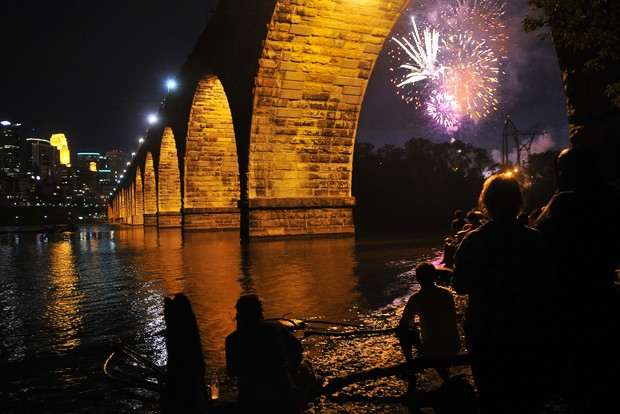 More than 100 spectators gather at the base of the Stone Arch Bridge to watch fireworks over St. Anthony Main Sunday.